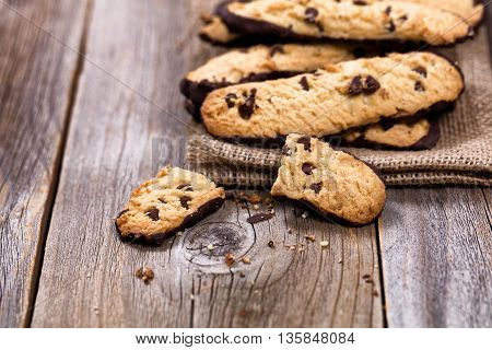 Close up of chocolate chip cookies on linen napkin with rustic wood. Selective focus on broken cookies in forefront of image.