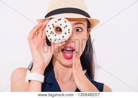 What a surprise. Portrait of cheerful delighted beautiful woman holding donut and expressing wonder while standing isolated on white background