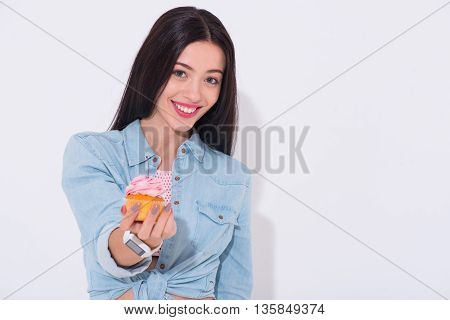 That is for you. Cheerful emotional beautiful woman smiling and holding cupcake while standing isolated on white background