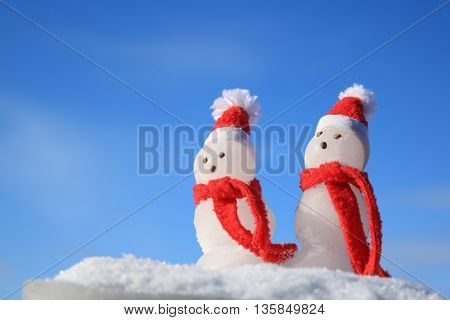 Snowmen with red scarves Isolated against a blue sky.