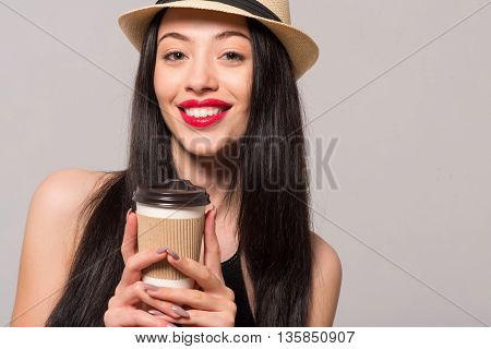 Cheer up. Positive delighted beautiful woman smiling and drinking coffee while expressing joy