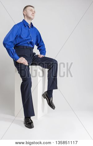 Caucasian Man Sitting on White Box and Looking Upwards. Posing Against White. Vertical Image Orientation