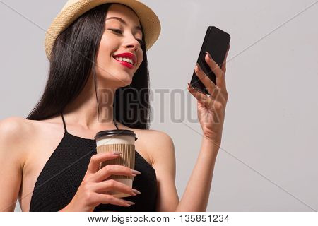 Call me. Cheerful delighted beautiful woman holding cell phone and drinking coffee while expressing joy