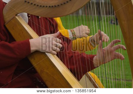 Two harps. Harp strings close up hands