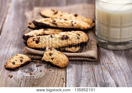 Close up of chocolate chip cookies in linen napkin with milk on rustic wood. Selective focus on broken cookies in forefront of image.