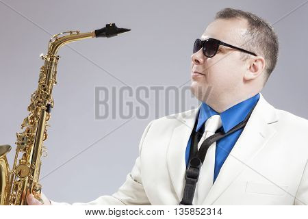 Portrait of Handsome Caucasian Saxophone Player With Music Instrument in Front. Posing Against White. Horizontal Image Composition