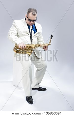 Full Length Portrait of Passionate Expressive Male Alto Saxophone Player in White Suit. Posing Against White Background. Vertical Image Composition