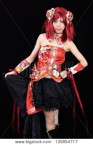 Young asian girl dressed in cosplay costume on black background