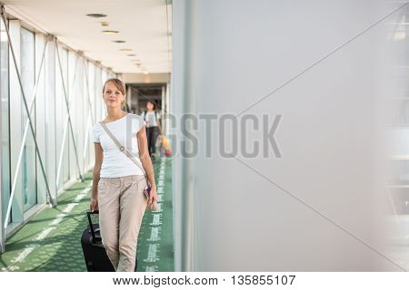 Portrait of a young woman in the boarding bridge, boarding an aircraft (color toned image; shallow DOF)