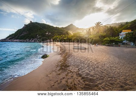 Tropical sandy beach with hills and blue sea