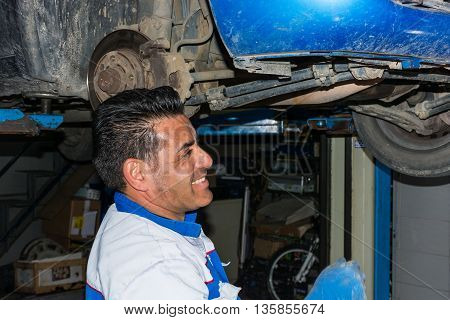 Automotive specialist adjusting an engine in his garage closeup of an experienced mechanic servicing a car at his workshop - Copyspace.