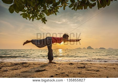 Young lady doing yoga stretch exercise on the beach at sunset