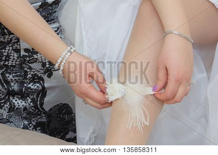 bridesmaid helping bride to put on garter bridesmaid dresses bride's garter