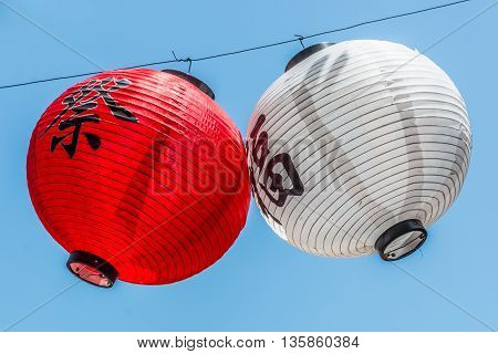 Two Japanese lanterns hanging from a wire with a blue sky background.