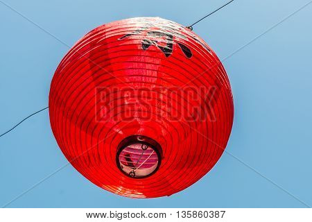 Single red Japanese lantern hanging on a wire with a blue sky background.