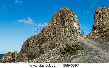 Man with bike going through Devils Gate Te Kopahou Reserve on the south coast of New Zealand.