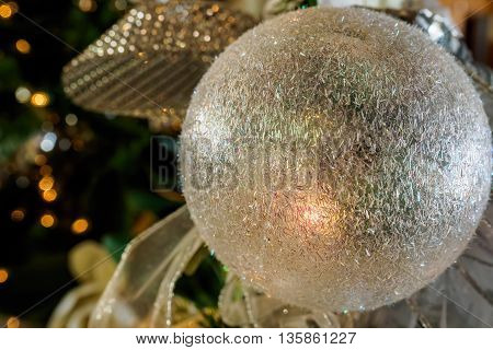 White Christmas bauble in closeup view. The tungsten lighting provides the image a warm feel.