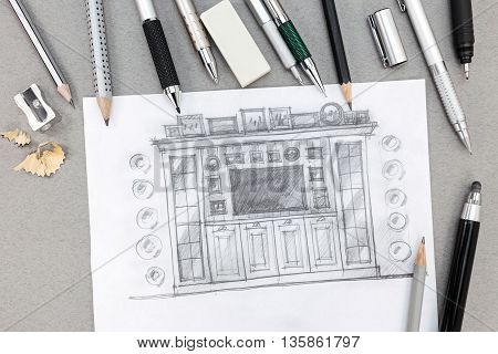 Freehand Sketch Design Of Wall Unit With Pens And Pencils On Table