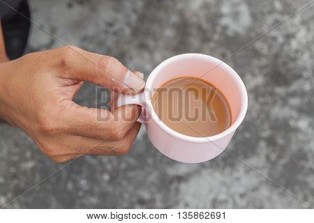 Young man holding a cup of coffee in cafe and soft-focus background,Top view.