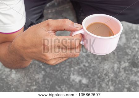 Young man holding a cup of coffee in the cafe and soft-focus backgroundselect focus front.