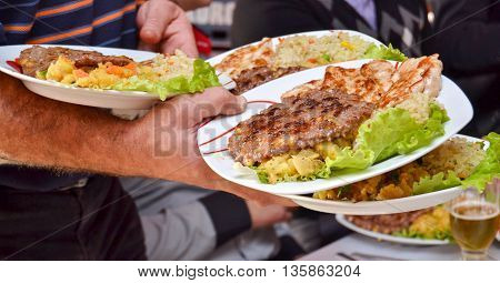 Picture of a A grilled chicken meat and burger serving in a bussy restaurant
