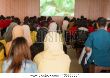 Blurred abstract background of university students sitting in a lecture room with  Movie screen , education high school, technology and people concept: Blurry view from back of the classroom: