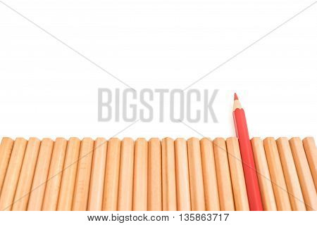 Sharp red color pencil stand out of group of brown pencils on white background - business concept of unique leader and success