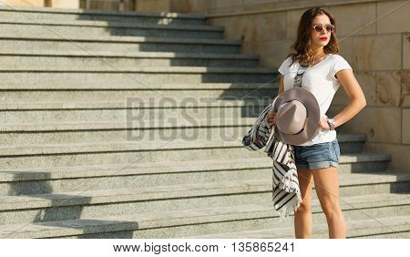 Beautiful woman standing on the stairs at hot summer day