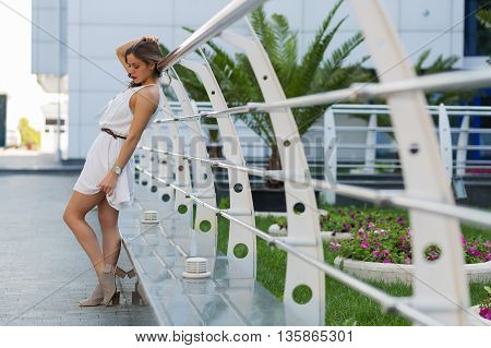 Beautiful woman in white dress standing on a city street