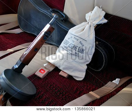 Gangster car with tommy gun, money sack, and violin case in the back seat.
