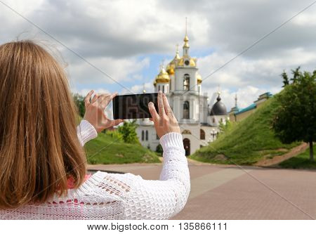 Girl taking pictures on mobile smart phone in front view Temple in the town of Dmitrov