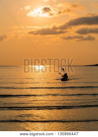 Silhouette of a lovely couple on a canoe boat during sunset. Silhouette of two people on a kayak at sea beach at twilight time