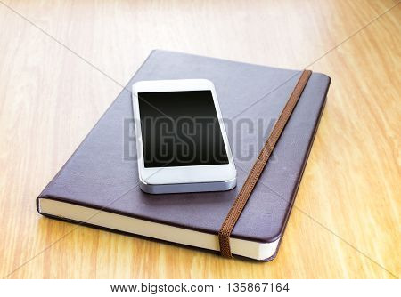 Blank Screen Smartphone On Brown Hard Cover Notebook With Elastic Strap On Wooden Table In Perspecti