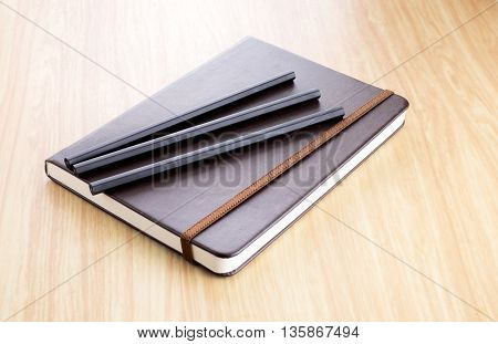 Three Black Pencil On Brown Hard Cover Notebook With Elastic Strap On Wooden Table In Perspective Vi