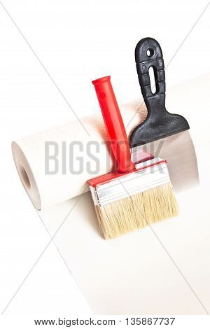 Brush spatula and roll of wallpaper isolated on white background