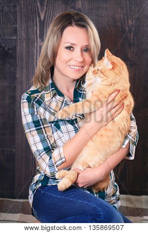 Portrait of a young attractive woman with a cat in hands studio shooting