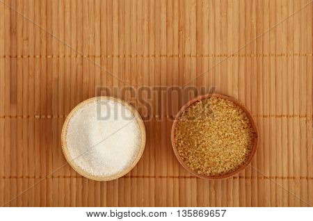 White And Brown Cane Sugar In Wooden Bowls On Mat