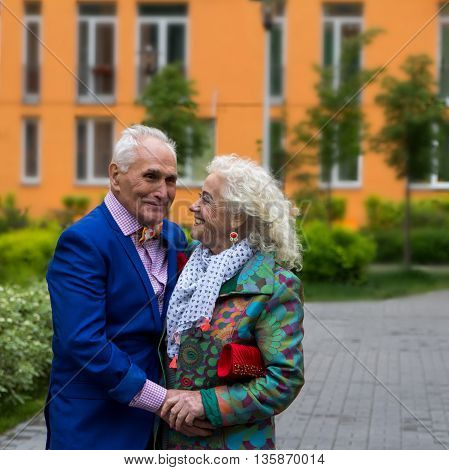 True love. Well-dressed elderly couple talking outdoors.