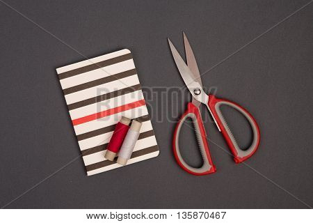 Grey And Red Thread, Scissors And Striped Notepad For Notes On Grey Background