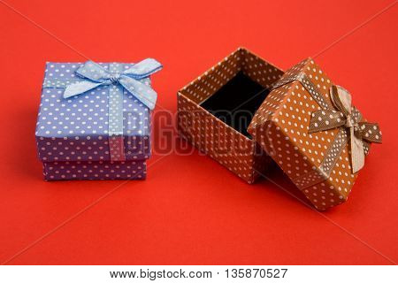 Celebratory concept - gift boxes in polka dots on red background