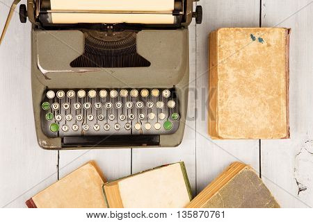 Retro Typewriter And Old Vintage Books On White Wooden Background