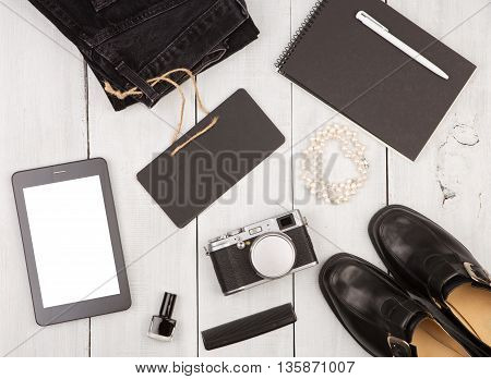Shoes, Jeans, Tablet Pc, Camera, Notepad, Essentials And Chalkboard On White Wooden Desk
