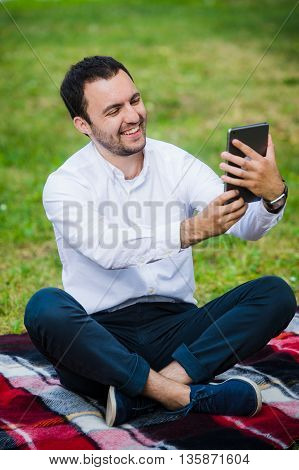 Modern young hispanic man taking a selfie at the park, with his tablet