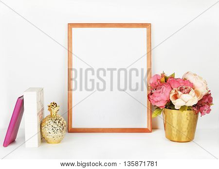 Wood picture frame with decorations. Mock up for your photo or text Place your work, print art,shabby style, white background, pastel color book, gold pineapple, peonies in gold vase.