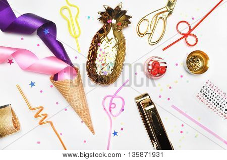 Glamour style background, flat lay. Gold and party items: Cocktail tubes apple, pear, spiral, ice cream cone, gold cosmetic bag, golden pineapple, stapler, scissors, paste. Desktop. view table, up.