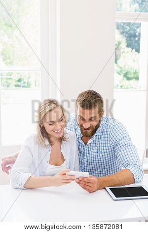 Smiling couple using a mobile phone at home