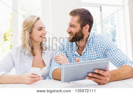 Smiling couple using digital tablet at home