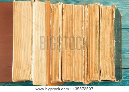 Stack Of Old And Used Hardback Books Or Text Books On Blue Wooden Background