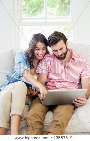 Happy couple sitting on sofa using digital tablet and laptop in living room