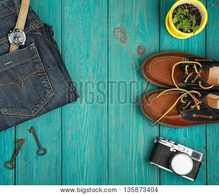 Shoes, Jeans, Camera, Watch And Vintage Keys On The Blue Wooden Desk